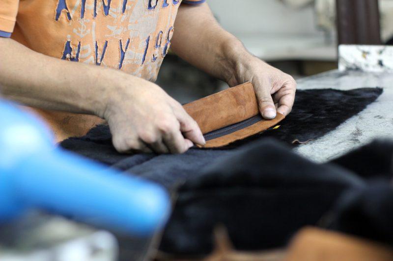 un artisan ajout un zip à un sac à main en cuir